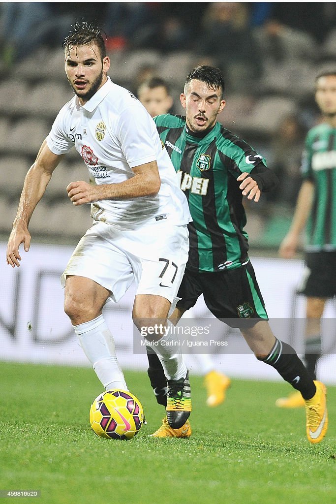 Panagiotis Tachtisidis # 77 of Hellas Verona FC ( L ) competes the ball with <a gi-track='captionPersonalityLinkClicked' href=/galleries/search?phrase=Nicola+Sansone&family=editorial&specificpeople=5525400 ng-click='$event.stopPropagation()'>Nicola Sansone</a> # 17 of US Sassuolo Calcio ( R ) during the Serie A match between US Sassuolo Calcio and Hellas Verona FC on November 29, 2014 in Reggio nell'Emilia, Italy.