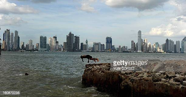 A Panamanian boy jumps into the water in the Panama Bay with the Panama City skyline in the back on January 19 2011 AFP PHOTO/ YURI CORTEZ