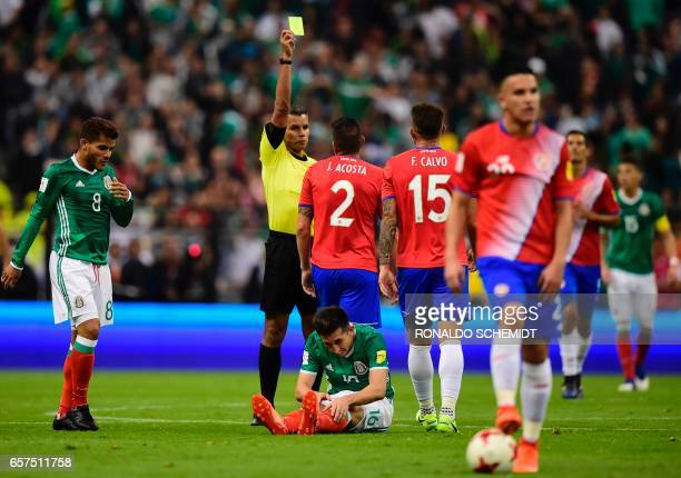 Panamanian referee John Pitti Hernandez shows the yellow card to Costa Rica's defender Johnny Acosta during their 2018 FIFA World Cup qualifier...