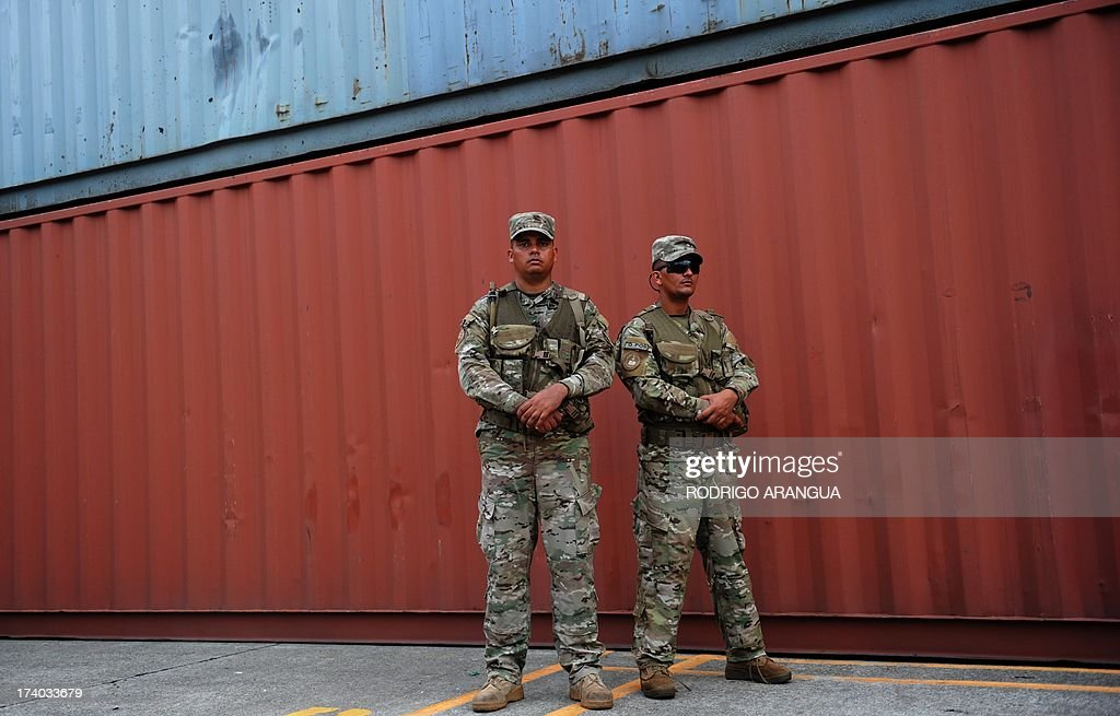 Panamanian soldiers guard containers (out of frame) of the North Korean Chong Chon Gang vessel where an alleged ageing Soviet-built radar control system for surface-to-air missiles was found, at the Manzanillo Port in Colon, 90 km from Panama City, on July 19, 2013. UN sanctions experts will go to Panama soon to investigate a North Korean ship that was intercepted carrying weapons, a US diplomat said Thursday. The vessel set out from Cuba and was trying to enter the Panama Canal when it was stopped by an anti-narcotics patrol, which later found the weapons concealed beneath several tonnes of sugar. AFP PHOTO / Rodrigo ARANGUA