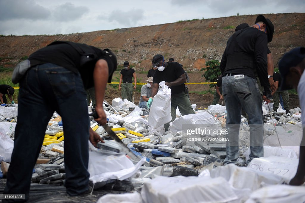Panama's anti-narcotics personnel prepare to burn packs with part of a seizure of 11 tons of cocaine and 388 kg of marijuana in Cerro Patacon, near Panama City on June 21, 2013 AFP PHOTO/ Rodrigo ARANGUA
