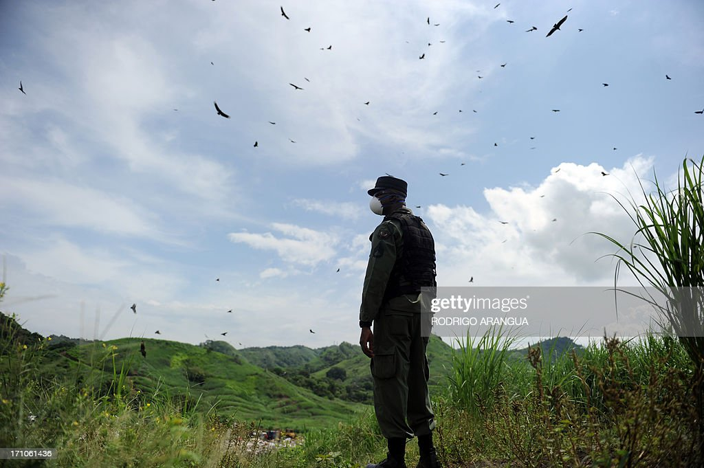 Panama's anti-narcotics personnel stand guard during the incineration of packs with part of a seizure of 11 tons of cocaine and 388 kg of marijuana in Cerro Patacon, near Panama City on June 21, 2013 AFP PHOTO/ Rodrigo ARANGUA