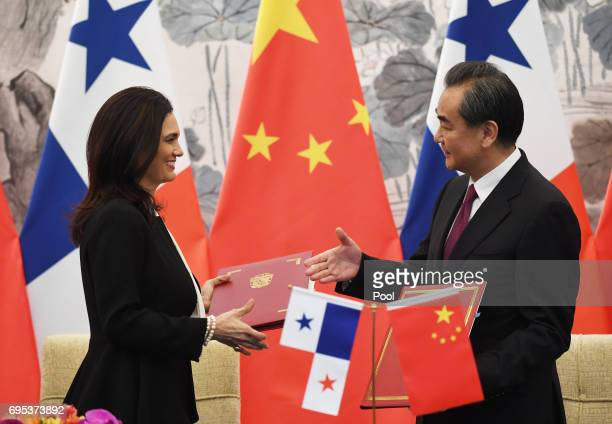 Panama's Foreign Minister Isabel de Saint Malo and Chinese Foreign Minister Wang Yi shake hands as they exchange documents after signing a joint...
