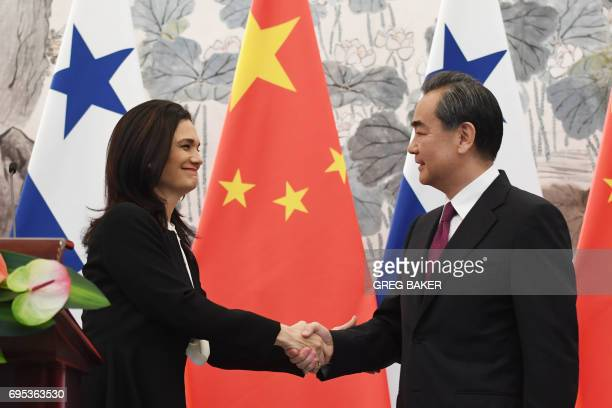 Panama's Foreign Minister Isabel de Saint Malo shakes hands with Chinese Foreign Minister Wang Yi during a joint press briefing in Beijing on June 13...
