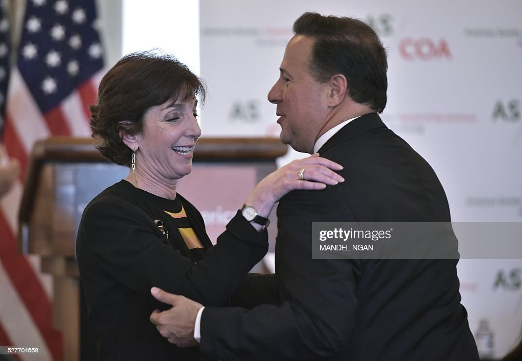 Panama's President Juan Carlos Varela (R) embraces US Assistant Secretary of State for Western Hemisphere Affairs Roberta Jacobson (L) at a luncheon during the Washington Conference on the Americas at the State Department on May 3, 2016 in Washington, DC. / AFP / MANDEL