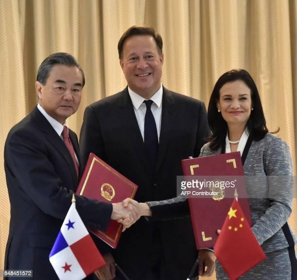 Panama's President Juan Carlos Varela smiles as Chinese Foreign Minister Wang Yi and his Panamanian counterpart Isabel De Saint Malo shake hands...