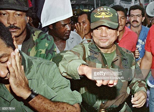 Panamian leader General Manuel Antonio Noriega fakes a punch to a supporter 02 May 1989 at the laying of the foundation of a group home in the...