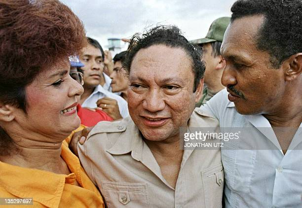 Panamian military strong man General Manuel Antonio Noriega smiles with supporters who embrace him 14 June 1987 upon his arrival in the small remote...