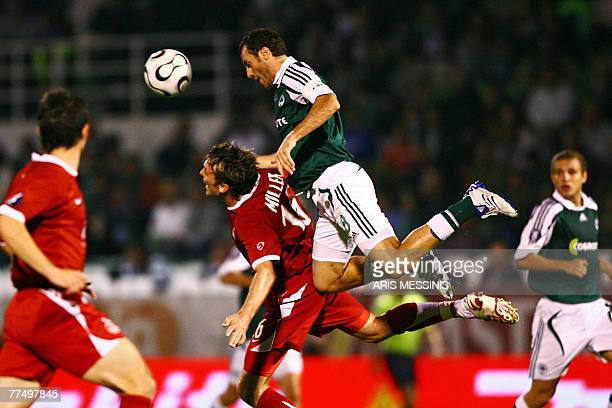 Panathinaikos' Ioannis Goumas challenges for the ball with Aberdeen's Lee Miller during their UEFA Cup first round football game in Athens 25 October...