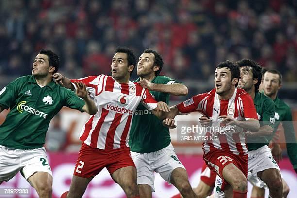 Panathinaikos' Loukas Vyntra and Ioannis Goumas challenge for a long ball with Olympiakos' Christos Patsatzoglou and Vassilis Torosidis during their...
