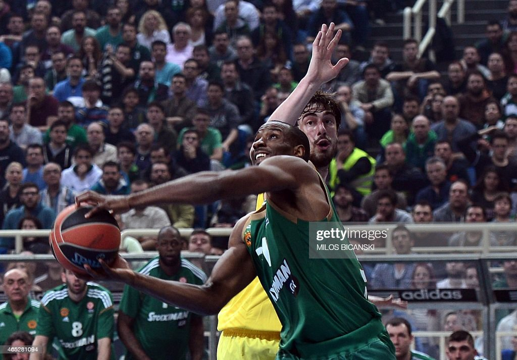 Panathinaikos player Lawal Gani (L) shoots to score as Barcelona's Croatian centre Ante Tomic looks on during their Euroleague top 16 basketball match at the olympic indoor hall in Athens on March 5, 2015. . AFP PHOTO/ MILOS BICANSKI