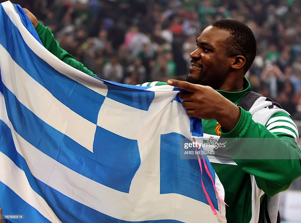 Panathinaikos' Sofoklis Schortsanitis celebrates holding a Greek flag after beating Anadolu Efes during the Euroleague top 16 basketball game in Athens on March 1, 2013.