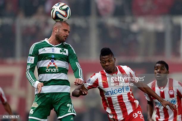 Panathinaikos' Spanish defender Nano heads the ball ahead of Olympiakos' Nigerian forward Michael Olaitan during the Greek Super League football game...