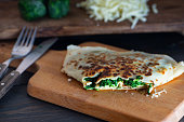 Pancakes filled with spinach and cheese on the wooden surface. Pancake week.  Maslenitsa.