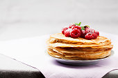 Stack of Russian-style pancakes with raspberries