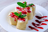 Pancakes stuffed with cottage cheese on a white plate, poured with jam and decorated with green mint leaves.