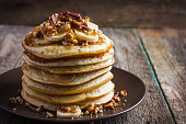 pancakes with banana, nuts and honey on wooden background