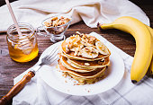 Pancakes with banana, walnuts and honey. Healthy breakfast. On dark wooden table background.