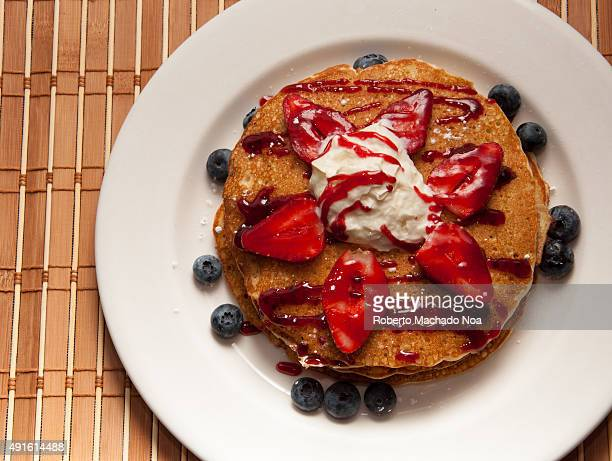 Pancakes with berries A short stack of pancakes sits on a white plate topped with whipped cream strawberries blueberries and strawberry syrup