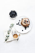 Pancakes with blueberries, coffee and a book served as lunch