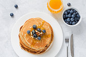Stack of pancakes with fresh blueberries, nuts and honey on white plate. Healthy breakfast food.