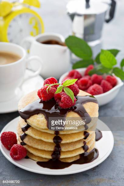 Pancakes with chocolate syrup and raspberries