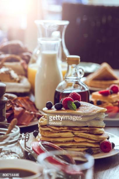 Pfannkuchen mit Ahornsirup, Beeren und frischen Kaffee