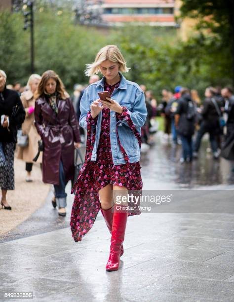 Pandora Skies wearing dress denim jacket red boots outside Christopher Kane during London Fashion Week September 2017 on September 18 2017 in London...