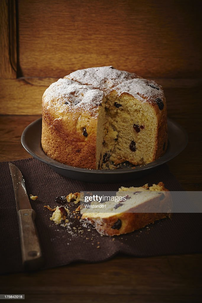 Panettone cake with cranberries and icing sugar on plate : Stock Photo