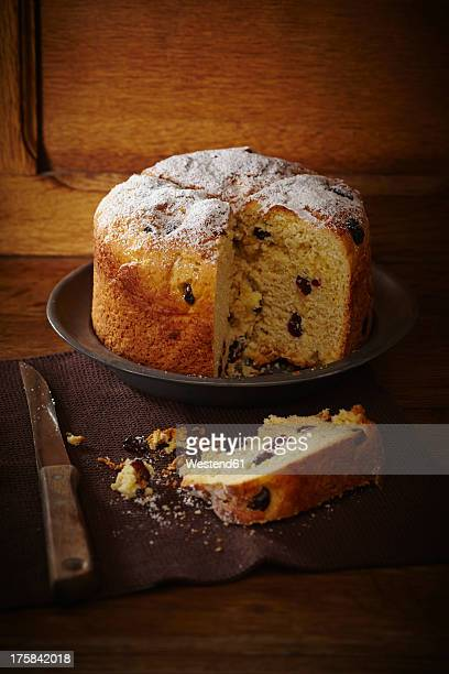 Panettone cake with cranberries and icing sugar on plate
