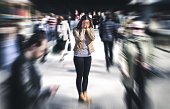 Panic attack in public place. Woman having panic disorder in city. Psychology, solitude, fear or mental health problems concept. Depressed sad person surrounded by people walking in busy street.