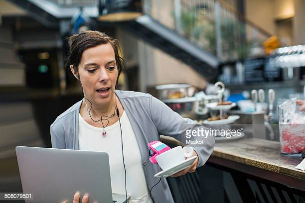 Panic mature woman holding laptop and coffee at cafe