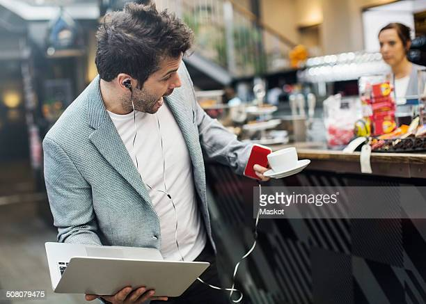 Panic mid adult man holding laptop and coffee at cafe