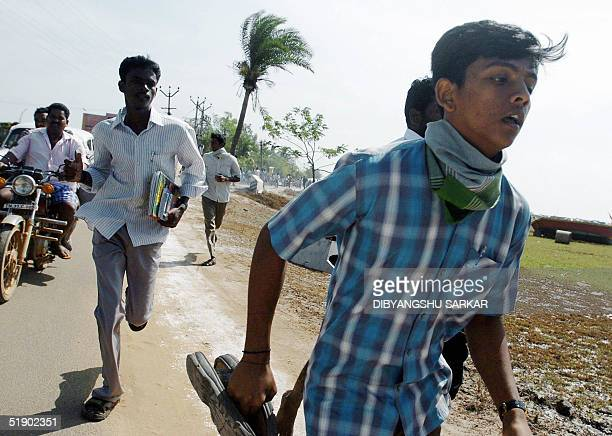 Panic sticken Indian people run for higher ground in Cuddalore some 185 Kms south of Madras 30 December 2004 after hearing the warning of possible...