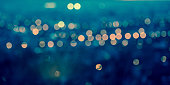 panorama city blurring lights abstract circular bokeh on toned blue background, closeup