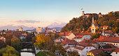Cityscape of the Slovenian capital Ljubljana at sunset. Ljubljana castle on hill above town. River Ljubljanica running trough city center. Karavanke mountains in background. Panorama.