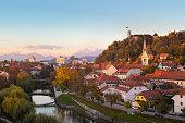Cityscape of the Slovenian capital Ljubljana at sunset. Ljubljana castle on hill above town. River Ljubljanica running trough city center. Karavanke mountains in background.