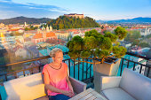 Female tourist enjoying in rooftop bar with panoramic view of Slovenian capital Ljubljana at sunset.