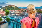 Female tourist enjoying panoramic view of Slovenian capital Ljubljana at sunset.