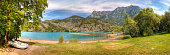 Panorama of sunny Lac de Serre-Ponçon lake with alps in background and a rowboat in the front