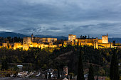 Panoramic view of Alhambra in Granada, a World Heritage Site by UNESCO, illuminated at night.
