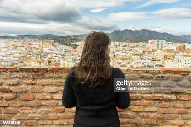 Panorama of the city of Malaga, Spain from the high stone walls. Young woman looking over the town on a sunny day with her back to the camera.