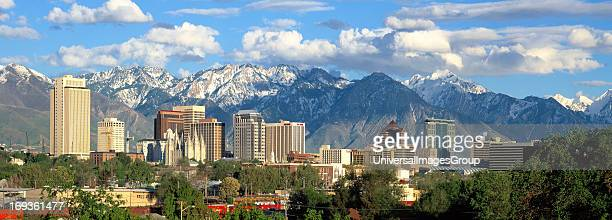 Panorama photo of the Salt Lake City Utah skyline showing downtown buildings and the snowcovered Wasatch Mountains in the background