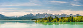 Panorama scene in Bavaria, Germany, with alps mountains mirroring in lake nearby city Fuessen in region Allgaeu
