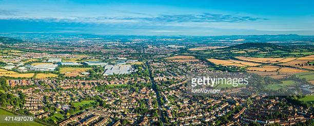 Panoramic aerial photo over suburban homes surrounded by green countryside