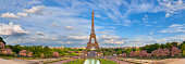 Paris, France. Panoramic image of Eiffel tower with fantastic clouds taken from fountains of Trocadero in Spring.