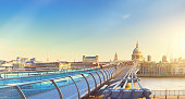 Panoramic image of Millenium bridge and St. Paul's cathedral across river Thames in the morning in London, UK. Toned panoramic image.