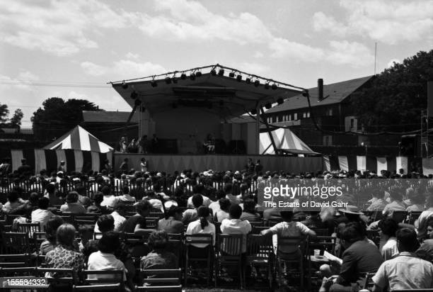 A panoramic image of the entire performance stage and the audience attending the Newport Folk Festival in June 1960 in Newport Rhode Island
