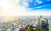 Business and culture concept - panoramic modern city skyline bird eye aerial view under dramatic sun and morning blue cloudy sky in Tokyo, Japan