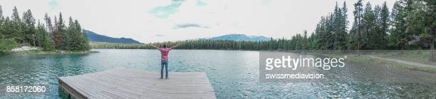Panoramic of young man arms outstretched on lake pier